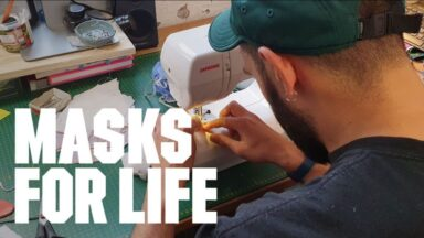 Man on sewing machine sewing a mask for life Islington Mill launches Masks for Life