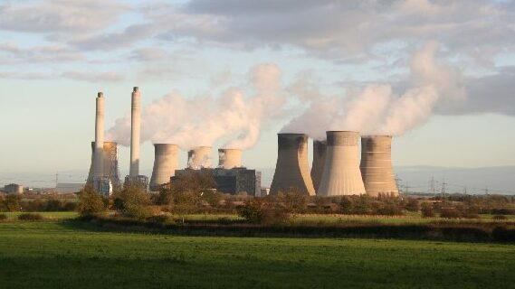 Coal powered power plant burning fossil fuels, smoke coming from the chimneys.