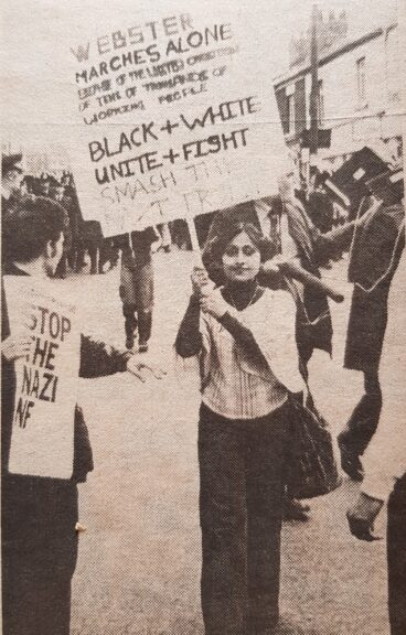 Ramila Patel with placard marching in front of Martin Webster, (Geoff Brown, left) Hyde, 8th October 1977. Photo: John Sturrock