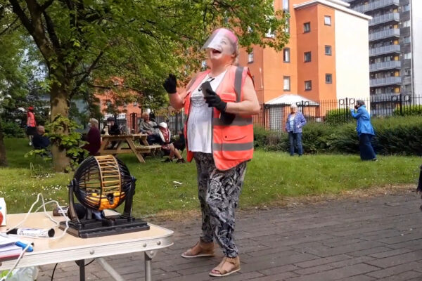 GM Savers network members performing outside a block of flats in Hulme.