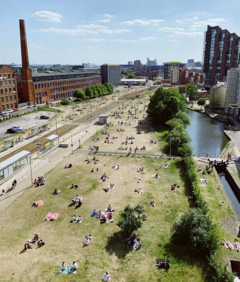 New Islington Green being enjoyed by local residents in the summer