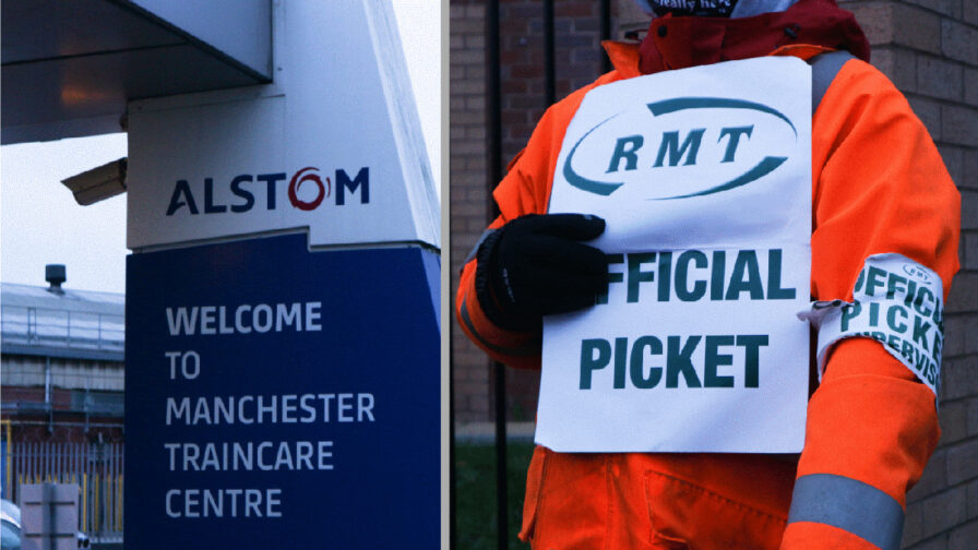Alstom sign outside Longsight depot with image of striking worker next to it.