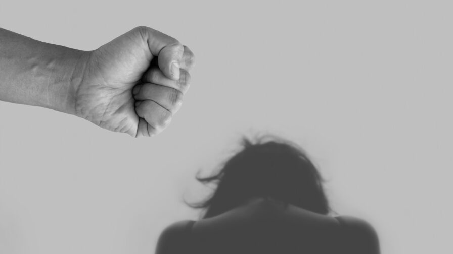 Black and white image of a hunched down person threatened by a clenched fist depicting domestic abuse
