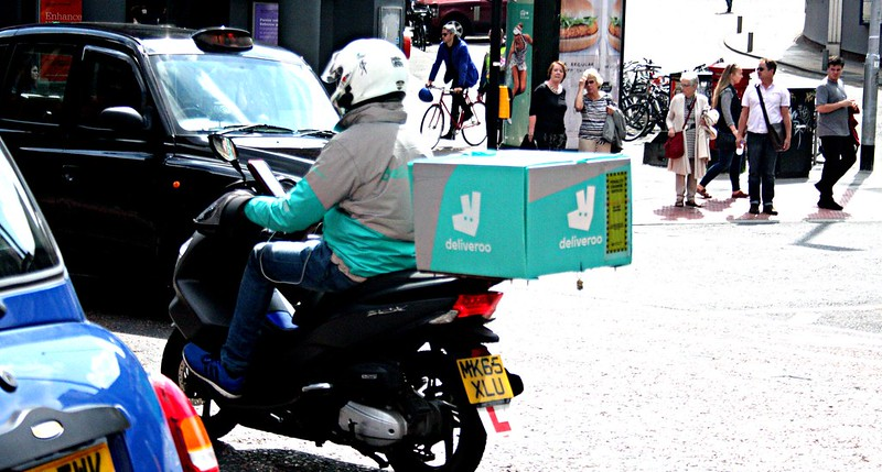 Deliveroo couriers on a scooter in Manchester