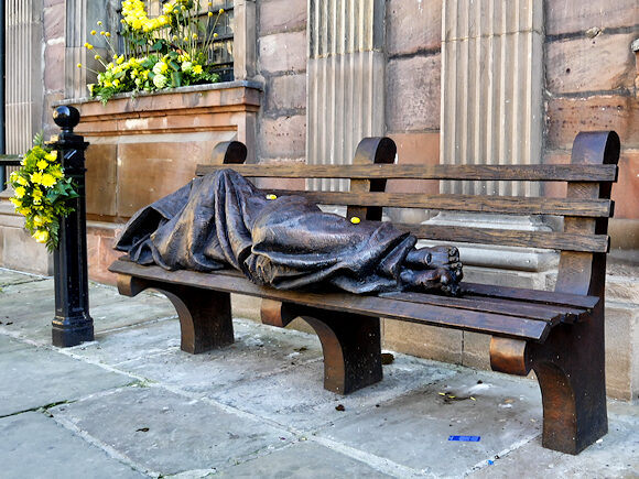 Homeless Jesus statue sleeping on a bench in Manchester
