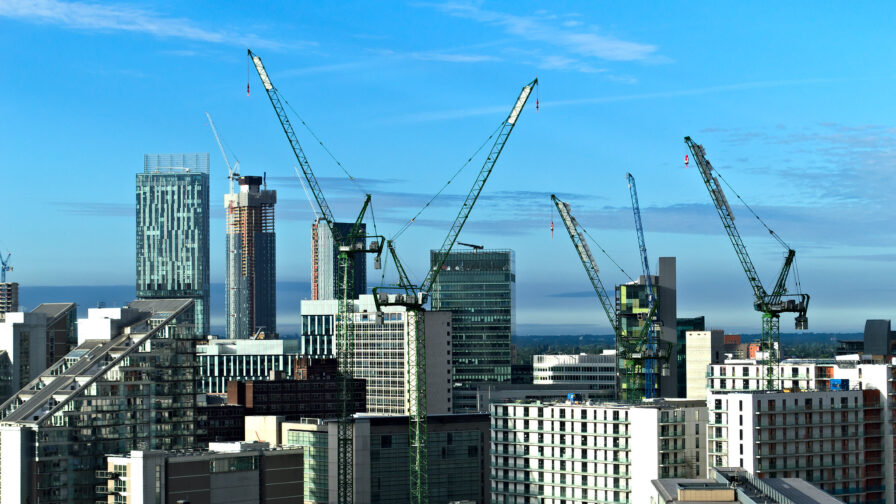 manchester city centre skyline with cranes, in article about council property deals.