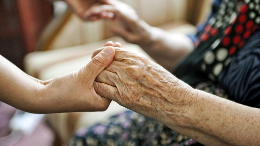 social care - close up shot of older and younger person holding hands.