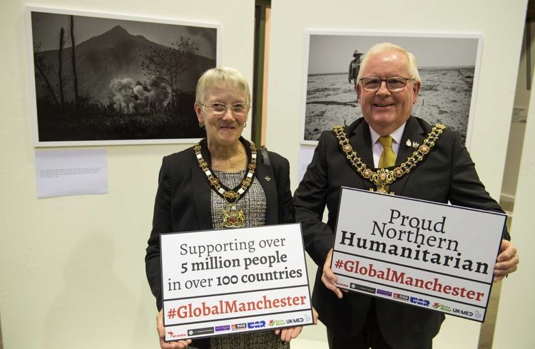 Manchester lord and lady mayoress holding up signs declaring manchester a humanitarian powerhouse.